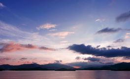 Mountain, cloud, gradient sky and ocean at sunset Royalty Free Stock Photos
