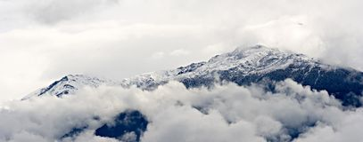 Mountain and clouds. Panorama of a mountain surrounded by clouds royalty free stock images