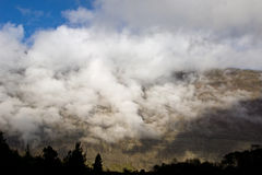 Mountain in the clouds. A beautiful view of a mountain covered in clouds Stock Photos