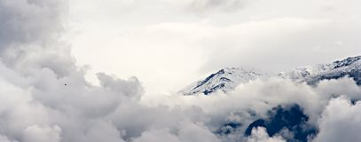 Mountain, clouds and a bird. Panorama of mountains with clouds and a bird flying Royalty Free Stock Photos