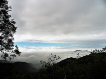 Mountain Clouds on High Overlook. Mountain overlook of overcast  skies below with streak of blue and forest  in foreground Royalty Free Stock Photography