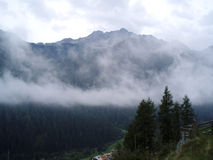 Mountain in clouds. Mountains with gentle clouds and trees Royalty Free Stock Images