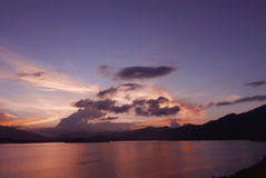 Mountain, cloudscape, dramatic sky and ocean at sunset Stock Photo