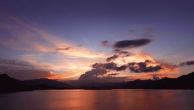 Mountain, cloudscape, dramatic sky and ocean at sunset Stock Images