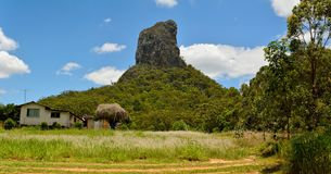 Mountain Coonowrin in Glass House Mountains region in Queensland. View of Mountain Coonowrin with a residential house in Glass House Mountains region in stock photography