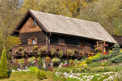 Mountain cottage decorated with hanging baskets. Traditional mountain wooden cottage in autumn colors on a hill Stock Image