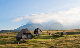 Mountain cottage landscape. Golden meadow with old abandoned mountain cottages and big mountain peaks in the background stock images