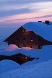 Mountain cottage at sunset in winter Royalty Free Stock Photography