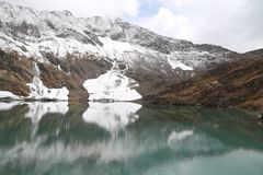Mountain covered by glacier and view of amazing lake under dark clouds. Mountains in autumn with brown and reddish grass under cloudy sky. Landscape image from stock image