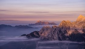 Mountain Covered With Snow and Fogs Under Blue Orange Sky Royalty Free Stock Image