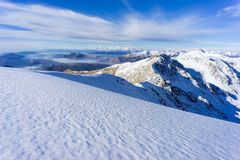 Mountain Covered With Snow Under White and Blue Sky during Daytime Royalty Free Stock Images