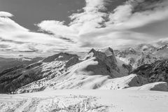 Mountain covered in snow with visible tree line. And interesting clouds spreading from the right Royalty Free Stock Image