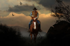 Mountain cowboy. A cowboy riding his horse in the mountains with a beautiful scenic sunset and trees and crows in the background Stock Photography