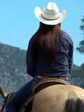 Mountain Cowgirl. Woman riding her horse through the mountains under a sunny blue sky royalty free stock photo