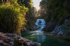 Mountain creek with cascade at sunset Royalty Free Stock Images