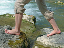Mountain creek and girls feet, doing kneippism. For hardening herself Stock Images