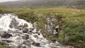 Mountain creek panorama with small waterfall and bridge, establishing shot stock video
