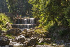 Mountain creek. Tourists relaxing on the banks of a mountain creek on a sunny spring day in Bucegi Mountains, Busteni, Romania Royalty Free Stock Photography