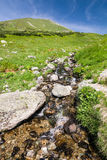 Mountain creek under peak and blue sky Royalty Free Stock Image
