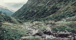 Mountain creek in valley. Mountain creek among green grass and stones in summer valley Royalty Free Stock Photo