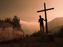 Mountain Cross. Silhouette of man supported by a mountain cross Lake Garda - italy as background stock image