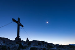 Mountain cross on peak with moon Royalty Free Stock Photography