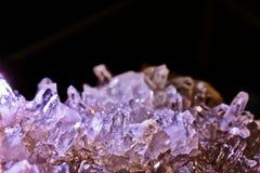 Mountain crystal stone on a black background purple look. Mountain crystal stone, purple look, on a black background, natural phenomenon, closeup photograph Stock Photo