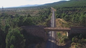 Mountain cyclist riding over bridge crossing track stock footage