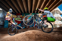 Mountain cyclists doing wheelie stunt on a mtb bike Stock Photo