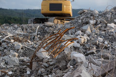 Mountain of debris with yellow excavator Royalty Free Stock Image