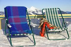 Mountain Deckchairs in the snow. Deckchairs at the top of a  ski mountain in the sun Stock Photography