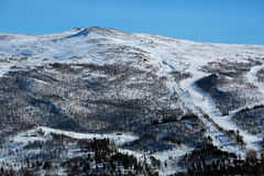 Mountain with downhill ski track, lift and timber cabins Royalty Free Stock Photos