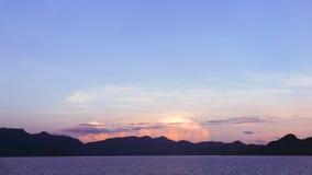 Mountain, dramatic sky and ocean at sunset Stock Photos