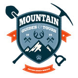 Mountain emblem. Mountain themed outdoors emblem with tools and axes Stock Photos