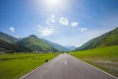Mountain empty road, green hills, blue sunny sky Royalty Free Stock Photos