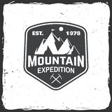 Vintage typography design with ice ax and mountain silhouette. Mountain expedition badge. Vector illustration. Concept for shirt or logo, print, stamp or tee Stock Images
