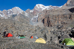 Mountain Expedition Camp in Morning. Four tents Yellow Green Red Located on Rocky Moraine Mountain View on Background with Glaciers People Walking and Preparing Royalty Free Stock Photo