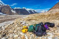 Mountain Expedition Luggage on Rocky Moraine of Glacier. Many Bags and Backpacks Peaks and Blue Sky royalty free stock image
