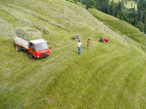 Mountain farmers with tractor. Schenna, Italien 07. July 2013 - high angle view on a steep alpine meadow with tractor and two field workers at work Stock Photo