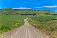 Mountain Farms Summer Dirt Road. Beautiful summers day in the mountains overlooking a small lake  dam in the valley of the mountain side. The green grass Stock Photography
