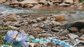 Mountain fast clean stream, on rocky shore, which has garbage, plastic bottles, bags. The human factor in environmental