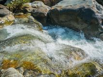 Mountain fast flowing river stream of water in the rocks.  Stock Photos