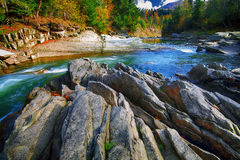 Mountain fast flowing river stream of water in the rocks at autumn. Mountain fast flowing river stream of water in the rocks with blue sky at autumn time royalty free stock photos