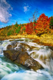 Mountain fast flowing river stream of water in the rocks at autu Royalty Free Stock Photos