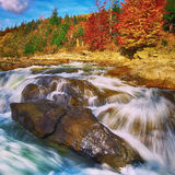 Mountain fast flowing river stream of water in the rocks at autu. Mountain fast flowing river stream of water in the rocks with blue sky at autumn time Stock Photos