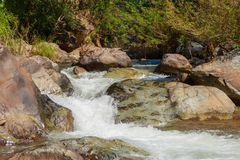 Mountain fast flowing river stream of water in the rocks.  Stock Photo