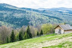Mountain farm in Carpathians, Ukraine. Mountain fenced farm on a hill of Carpathians, Ukraine. Panoramic view to the forest and mountain peaks. Wooden ascetic royalty free stock images