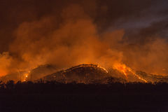 Mountain Fires. Fires burning uncontrolled through a mountain range at night Stock Image