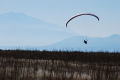 Mountain Flight. A paraglider glides over a mountain field freely Royalty Free Stock Photo