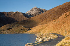 Mountain footpath. A footpath curves around a mountain lake with steep grass banks and rocky mountain cliffs in the distance Royalty Free Stock Images